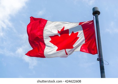 Canadian Flag in the wind over blue sky with clouds