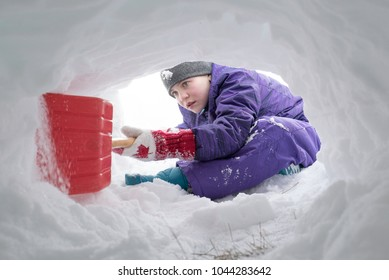 Canadian girl digging snow tunnel with red plastic shovel