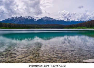 Canadian Lake. Unique reflection and beautiful colors. Mountains in the back and rock in front under water. Wonderful canvas!