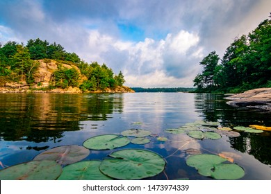 CANADIAN LANDSCAPE DURING MORNING SUNRISE - Beautiful lily pads and forested rock cliffs on lake in Canada, with summer clouds in sky reflecting in water. Canadian bluffs. Muskoka, Ontario, Canada