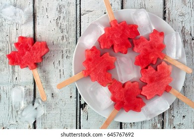 Canadian maple leaf watermelon pops on a plate against a rustic old white wood background