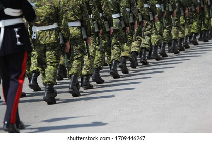 Canadian military and RCMP in uniform and armed marching in a line on the street in York Region