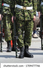 Canadian military soldiers standing on duty with their guns in a street parade