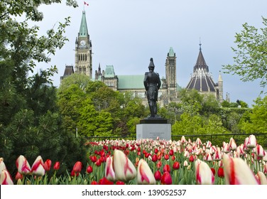 The Canadian Parliament Centre Block and Library with the statue of Colonel John By  during spring with many red and white tulips.
