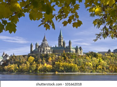 The canadian Parliament framed with Autumn leaves across the Ottawa river.
