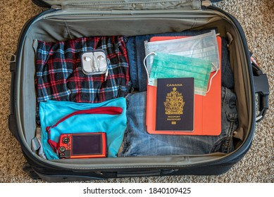 Canadian passports and masks with travel items in a suitcase.