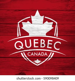 A Canadian province crest on a background of distressed barnboard. The shield features a maple leaf and the main text says Quebec, Canada.