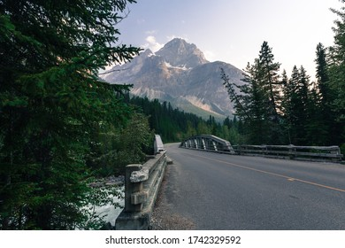 Canadian Rockies local road with a mount on a background and a small bridge across a water stream