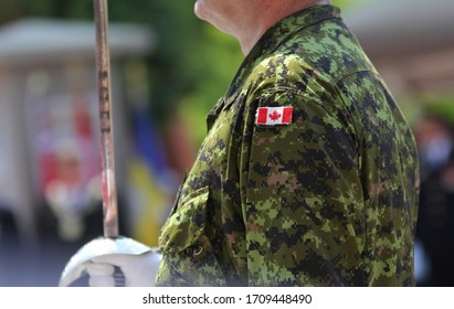 Canadian soldier in uniform waring white gloves and holding sword and wearing a Canadian flag