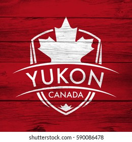 A Canadian territory crest on a background of distressed barnboard. The shield features a maple leaf and the main text says Yukon, Canada.