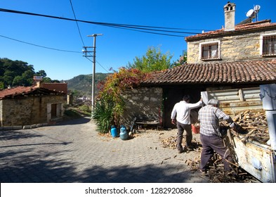 Canakkale, Kucukcetmi / Turkey - October 15, 2017: Two local men are unloading a truck full of wood at village