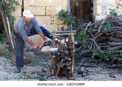 Canakkale, Nusratli / Turkey - October 15, 2017: A man cutting wood in front if his house by a sawing machine