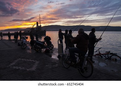 CANAKKALE, TURKEY - 9th of February, 2013: Fishermen silhouettes on the coast fishing in the sunset in urban environment; Canakkale, Turkey.