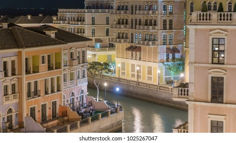 Canal aerial top view in Venice-like Qanat Quartier of the Pearl precinct of Doha night timelapse, Qatar. Evening illumination reflected in water