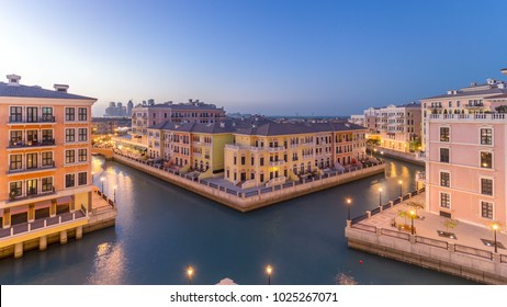 Canal aerial top view in Venice-like Qanat Quartier of the Pearl precinct of Doha day to night transition timelapse, Qatar. Evening illumination reflected in water