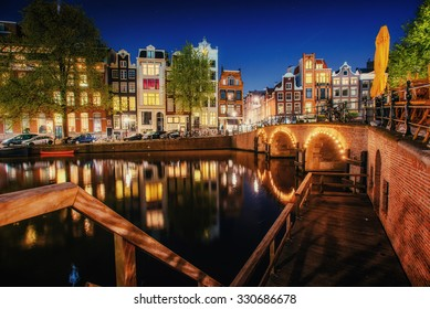 Canal in Amsterdam at night. Highlighting buildings and streets and is reflected in the water