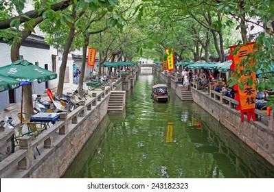 A canal in ancient Tongli watertown near Suzhou with traditional boats and old houses on both sides, Jiangsu province,  stylized and filtered to resemble an oil painting