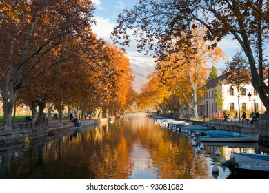 The canal in Annecy ringed by the beautifully colored autumn tree leaves during changing of seasons on a clear sunny, blue sky day in France. Horizontal