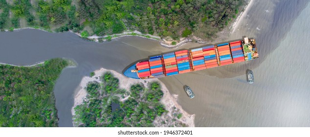 Canal blocked by huge cargo container ship; Aerial top view of accident container ship a stranded ship with salvage crews across the canal concept accident safety and insurance.