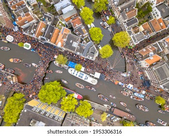 Canal boat parade on Koningsdag Kings day festivities in Amsterdam. Birthday of the king. Seen from helicopter.