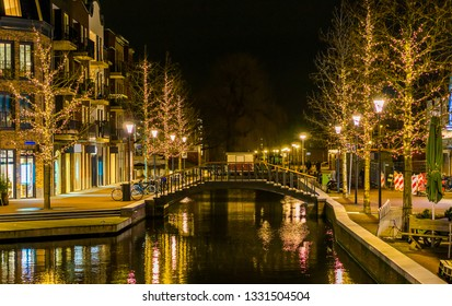canal bridge in the center of Alphen aan den Rijn, The netherlands, decorated trees with lights, Dutch city Architecture