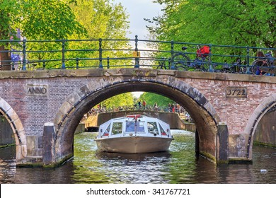 Canal cruise boat goes under the bridge over the Leidse canal at the Patricians' or Lords' canal (Herengracht) in Amsterdam in spring