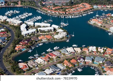 A canal estate featuring waterfront luxury living including private pools, marina and vessels.  Also includes a road and railway line and train. In Brisbane, Queensland Australia.