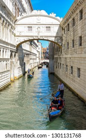 Canal with gondolas in Venice, Italy - September 2018. Summer sunny day. Venetian gondolier punting gondola through green waters of Venice canal. Picturesque view of Gondolas on lateral narrow canal.