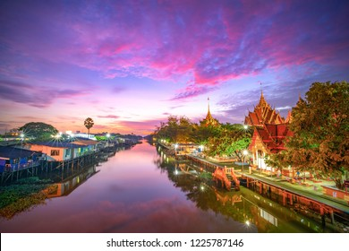 Canal House and temple Thai Culture under sunrise sky.