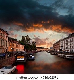 Canal with Moyka river in Saint-Petersburg with dramatic cloudy evening sky. View from Nevsky Prospect.