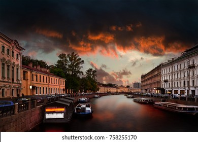 Canal with Moyka river in Saint-Petersburg with dramatic cloudy evening sky. Horizontal view from Nevsky Prospect.
