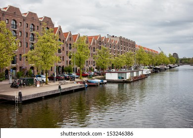 Canal and quayside buildings of Entrepotdok in Amsterdam, converted from old warehouses into apartments, offices, cafes in Holland, Netherlands.