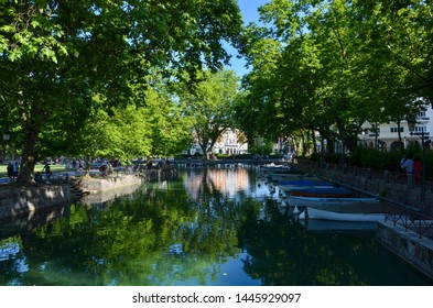 A canal of river Thiou in the alpine city of Annecy in Haute Savoie in France, view from waterfront to the small port and downtown, people are walking alongside the riverbank, a sunny day in summer