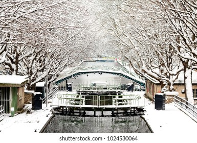 The Canal Saint-Martin in Paris by winter. Trees and the bridge over canal are covered with fresh snow - atmosphere is peaceful and zen-like.