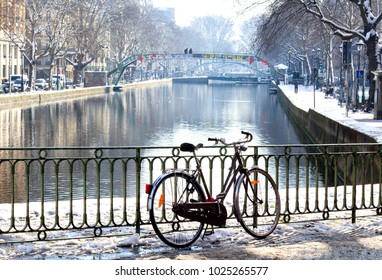 The Canal Saint-Martin in Paris by winter with snow covering canal banks and trees along the side of the canal.