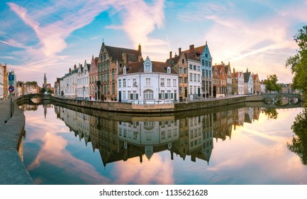 Canal Spiegelrei, bridges and tourist boat at sunset in Bruges, Belgium