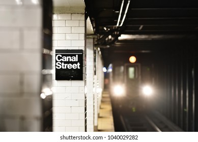 Canal Street station in New York City's subway system, with approaching train lighting up tracks.