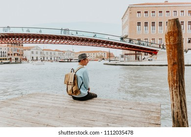 The canal in Venice, Italy. A city of love and romance. A young man enjoys the view. Modern colors. Background for the inscription. A popular place to travel. lane or bystreet.
