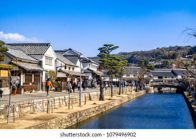 Canals of Kurashiki Bikan Historical Quarter with white traditional houses in Okayama, Japan in winter with blue sky