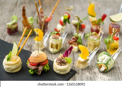 Canape, appetizers, on the table, buffet menu, European cuisine, shrimp, mini burger on a wooden background