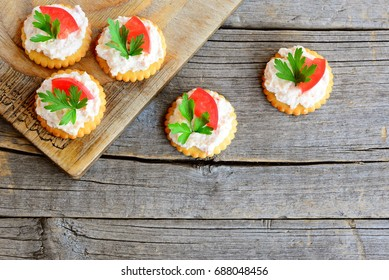 Canape cooked from salty crackers with spicy soft cheese, tomato slice and green parsley leaf. Spicy cheese canape on an old wooden background. Quick aperitif recipe. Top view