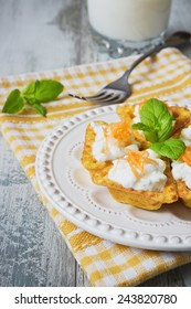 canape with cottage cheese and grated carrot on a plate on the old wooden background. a festive meal.
