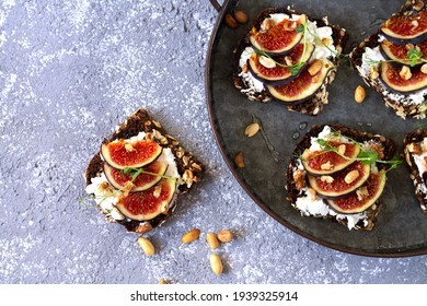 Canape, crostini or bruschettas with fresh figs, bread, cream cheese, honey on metal tray and slate background top view