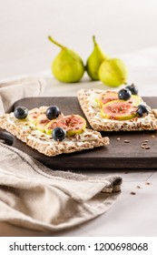 Canape or crostini with multigrain  crispread with cream cheese and fresh fig slices on a wooden board. Delicious appetizer ideal as an aperitif.