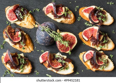 Canape or crostini with toasted baguette, cheese, onion jam, figs and fresh thyme on a slate board. Delicious appetizer, ideal as an aperitif. Top view