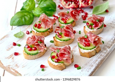 Canape or crostini with toasted baguette, light cheese, cucumber, pomegranate and salami on light background. Top view with copy space.