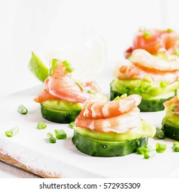 Canape with cucumber, avocado mousse, salmon and shrimp on white wooden background, selective focus
