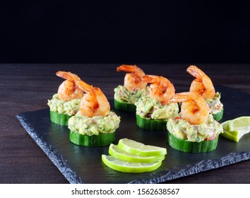 Canape with cucumber, avocado salad and shrimp on black slate platter against dark background