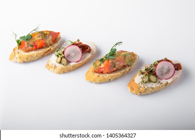 Canape mini bruskety sandwiches with fresh and steamed vegetables. Beautifully decorated catering banquet menu. Food snacks and appetizers for buffet. Isolated on white background