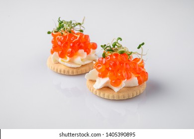 Canape portion cracker, butter, salmon red caviar. Beautifully decorated catering banquet menu. Food snacks and appetizers for buffet. Isolated on white background